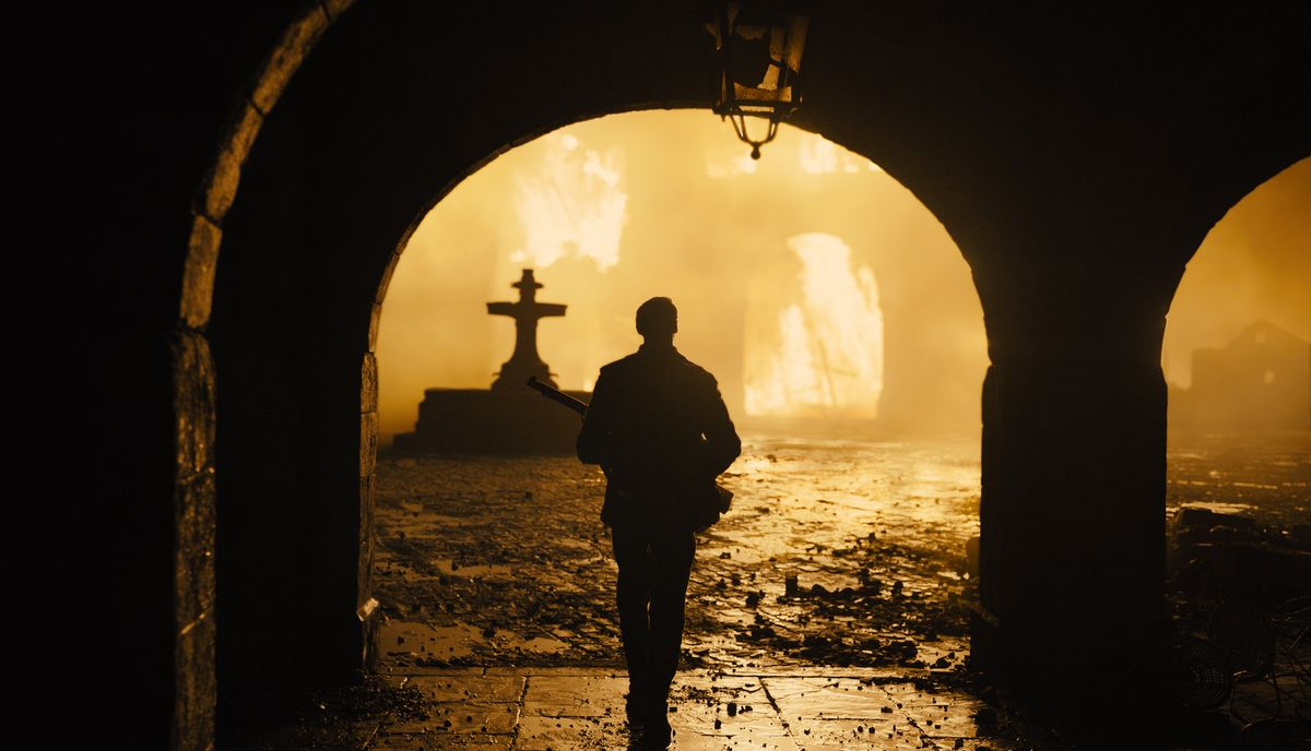 a soldier holding a rifle walks toward a firebombed town in silhouette in 1917