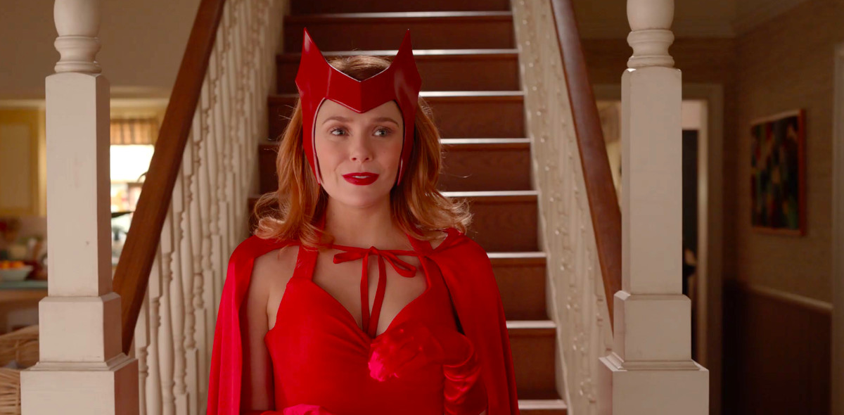 Elizabeth Olsen descends a staircase as Scarlet Witch in her classic costume, complete with gloves, cape, and hairpiece, in a clip from teaser for WandaVision.