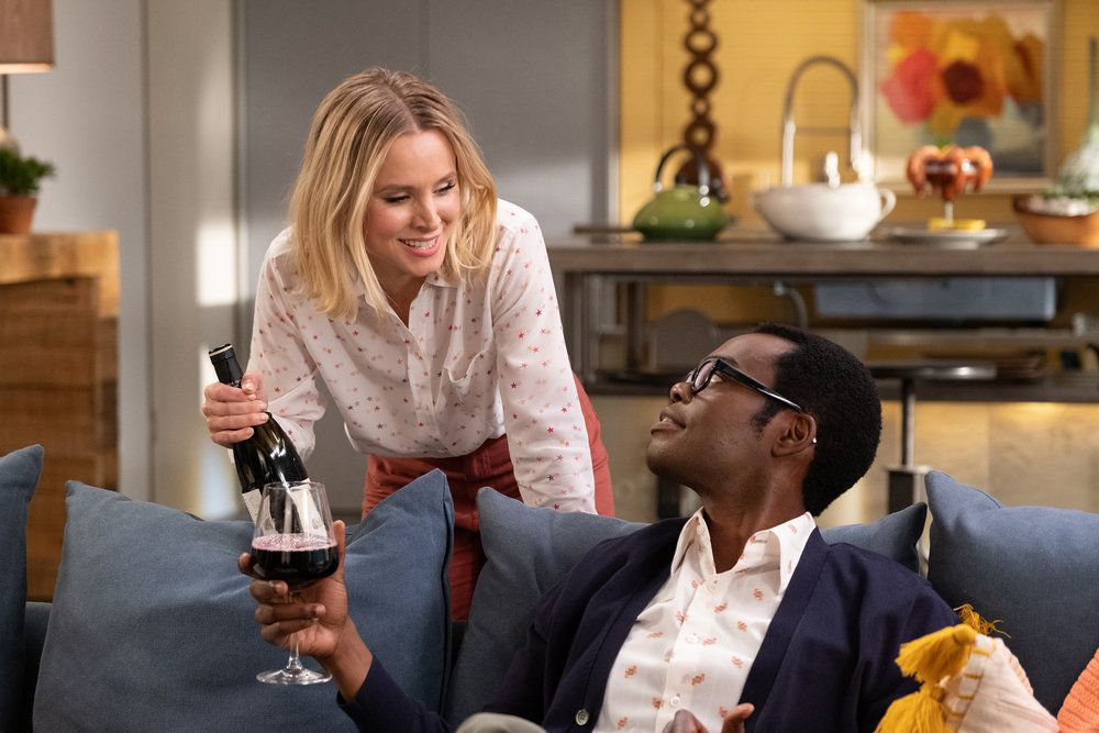 "Eleanor (Kristen Bell) and Chidi (William Jackson Harper) share a bottle of wine in a screenshot from The Good Place season 4, episode 13, ""Whenever You're Ready"""