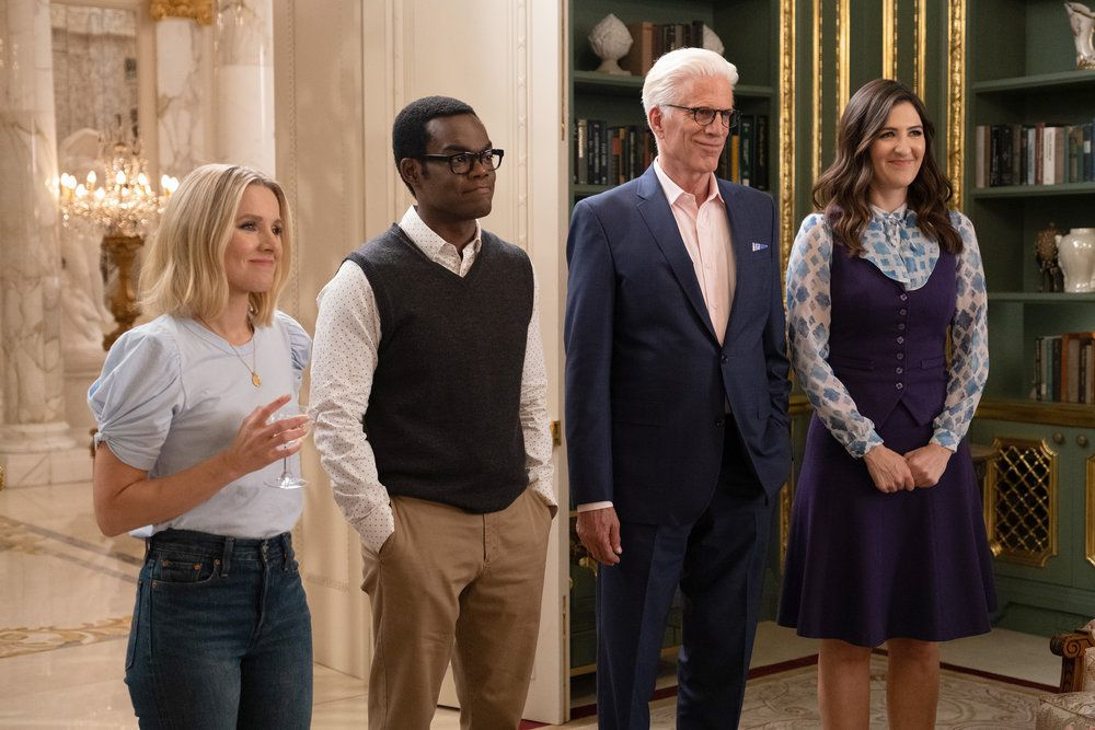 "Eleanor (Kristen Bell), Chidi (William Jackson Harper), Michael (Ted Danson), and Janet (D'Arcy Carden) smile in a screenshot from The Good Place season 4, episode 13, ""Whenever You're Ready"""