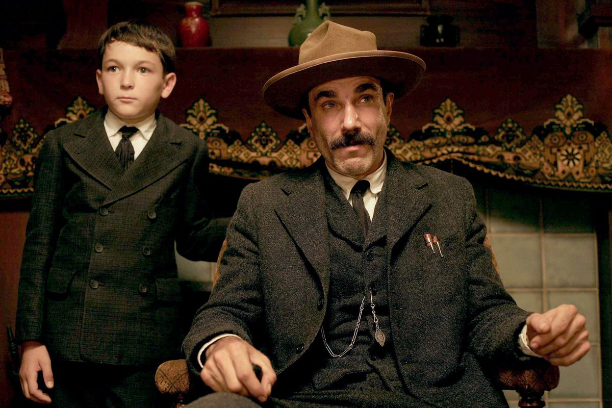 Dillon Freasier stands next to a seated Daniel Day Lewis in a screenshot from There Will Be Blood