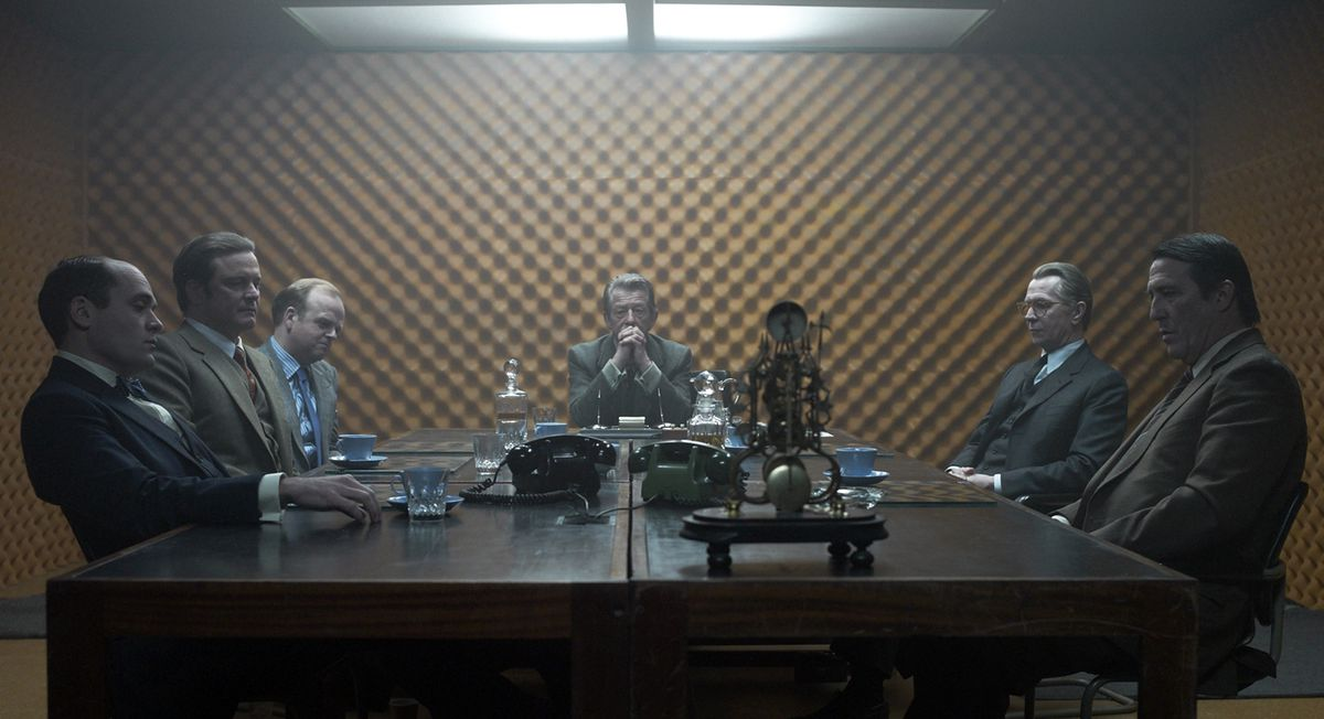 Some of the cast of Tinker Tailor Soldier Spy seated around a table.