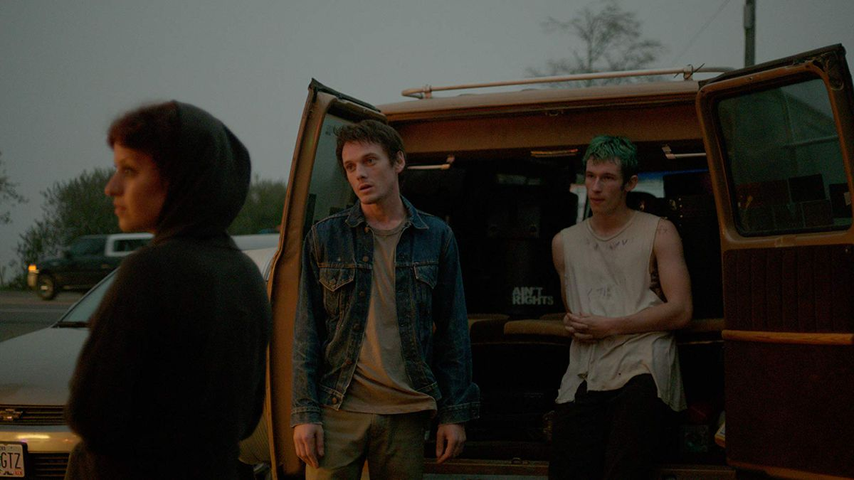Alia Shawkat, Anton Yelchin, and Callum Turner stand outside of a tour van in a screengrab from Green Room