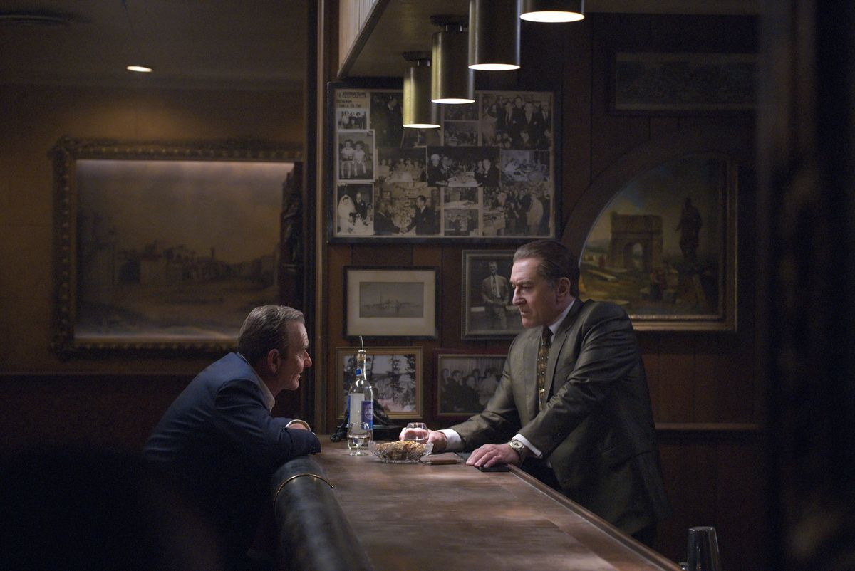 Pacino as Jimmy Hoffa and De Niro as Frank Sheeran across from each other at a bar in The Irishman