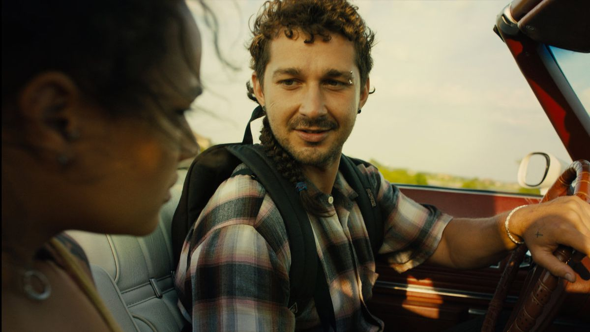 Shia LaBeouf drives a convertible and looks at Sasha Lane