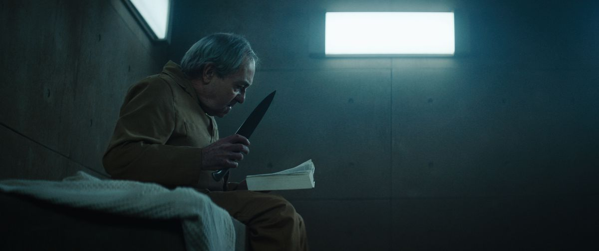 An elderly man clutching a nasty-looking knife and reading a book sits on his bed in a dimly lit concrete cell in The Platform.