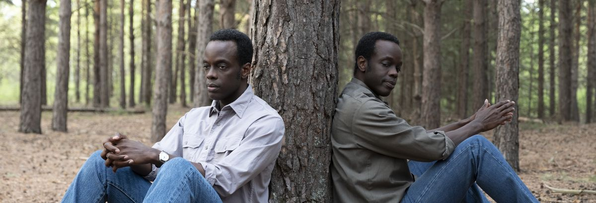 A young black main in jeans and a button-down shirt sits in the forest with his back against a tree, while a dopplegänger version of him in a darker shirt sits against the other side of the same tree.