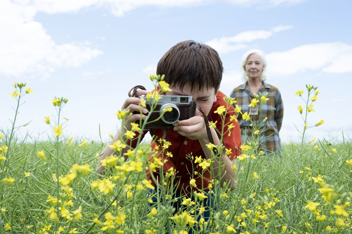 A boy in a bright red shirt uses an old-fashioned manual camera to take a closeup picture of a bright yellow flower as an older white-haired woman stands behind him and watches.