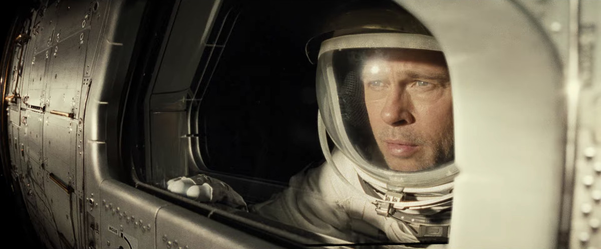 a view of Brad Pitt as an astronaut looking out from a spacecraft window