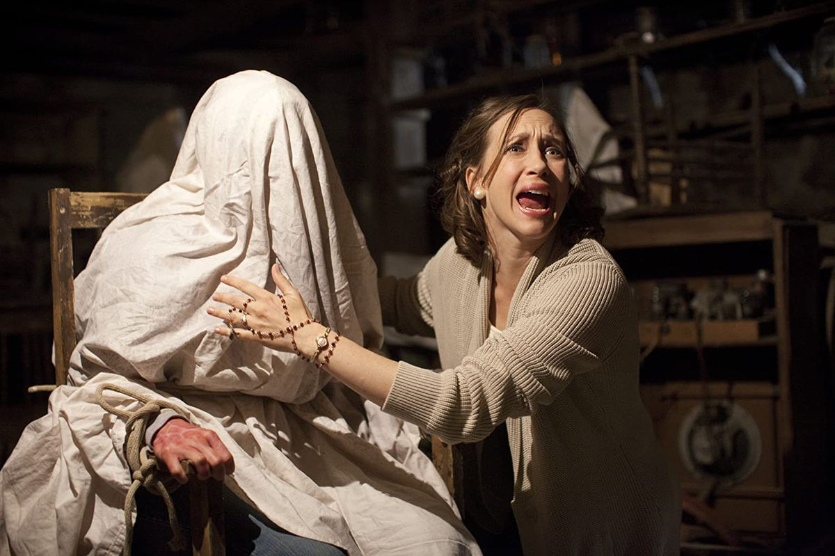 Lorraine Warren (Vera Farmiga) touches a woman covered in a sheet