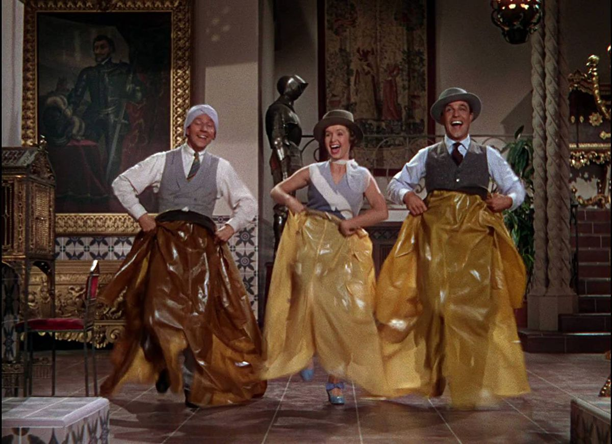 Gene Kelly, Debbie Reynolds, and Donald O'Connor dance with raincoats