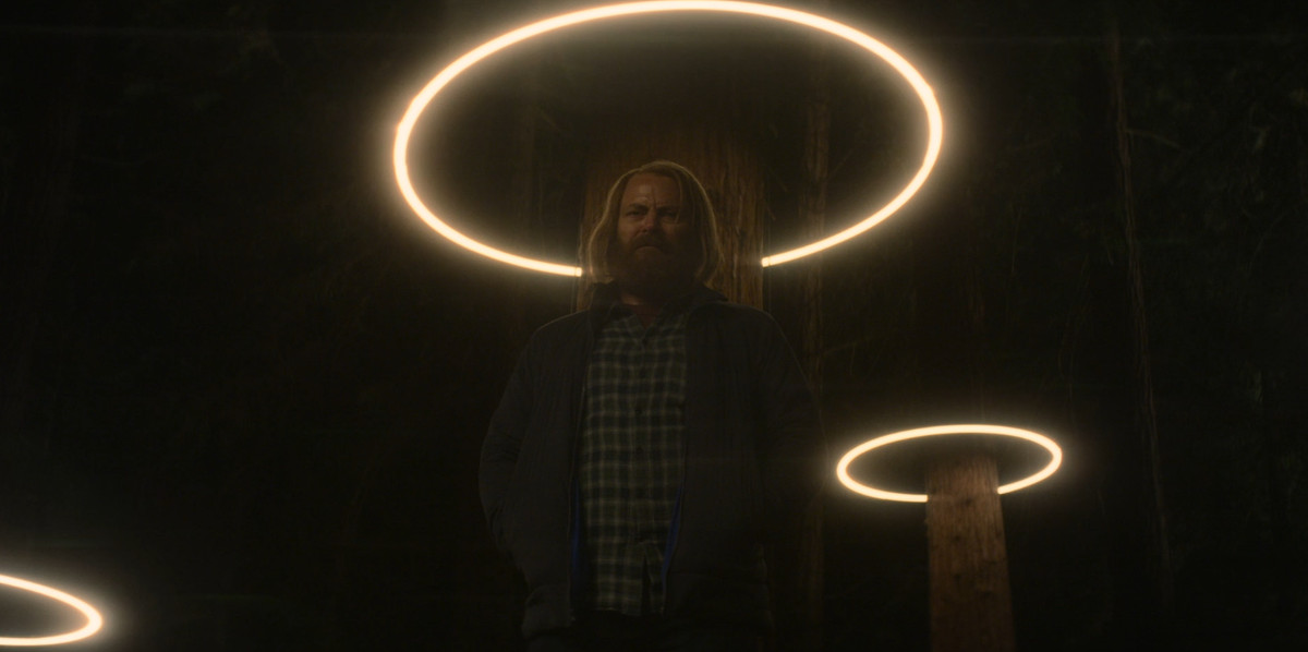 A character from Devs stands under a light, resembling a halo around his head