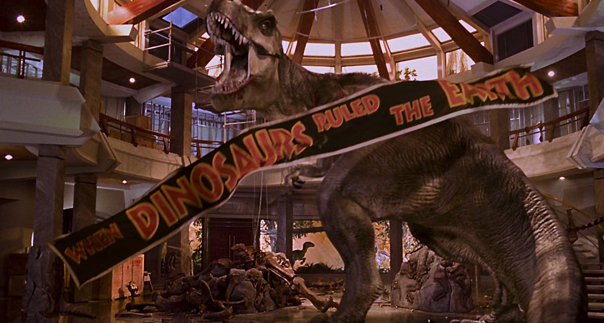 """jurassic park ending: the t-rex defeats the raptors in the jurassic park lobby as a """"when the dinosaurs ruled the earth"""" banner falls from the ceiling"""