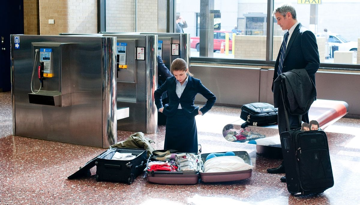 Anna Kendrick kneels in front of her spread-open luggage in an airport in Up in the Air, as George Clooney stands over her, watching.