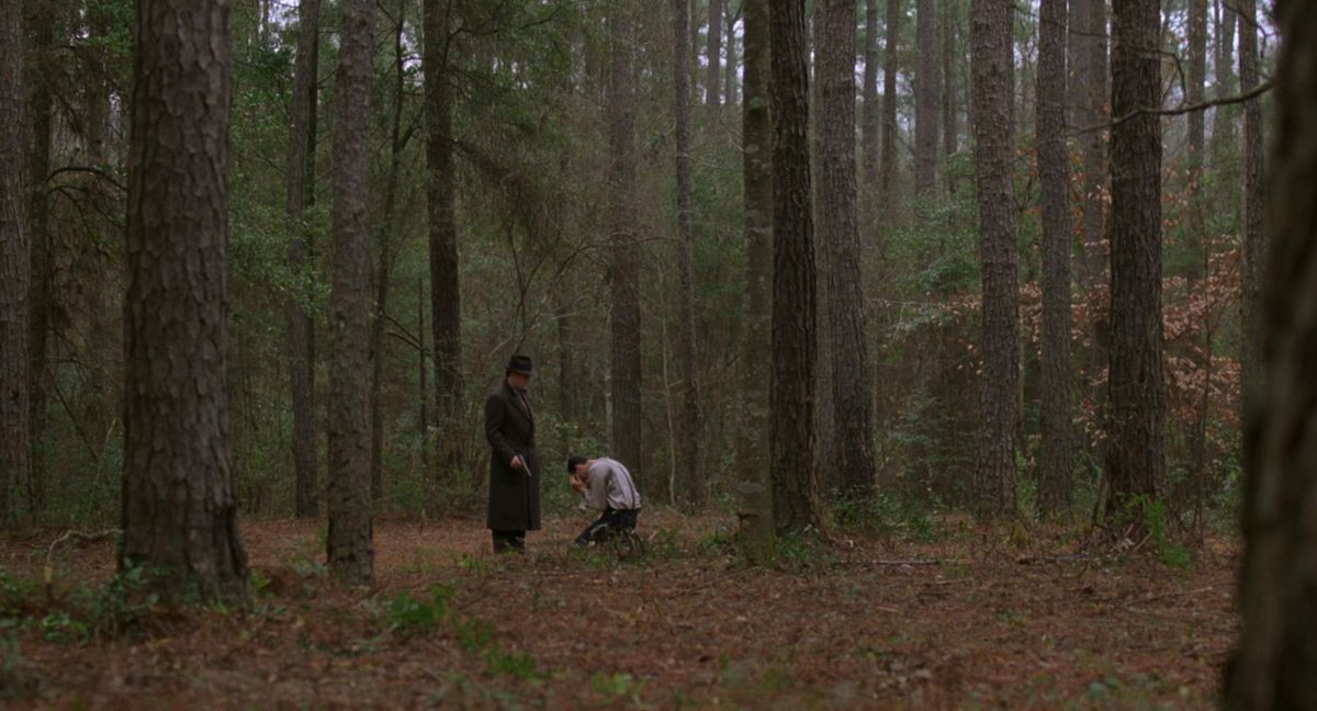 Miller's Crossing: gangster stands in the forest with a gun