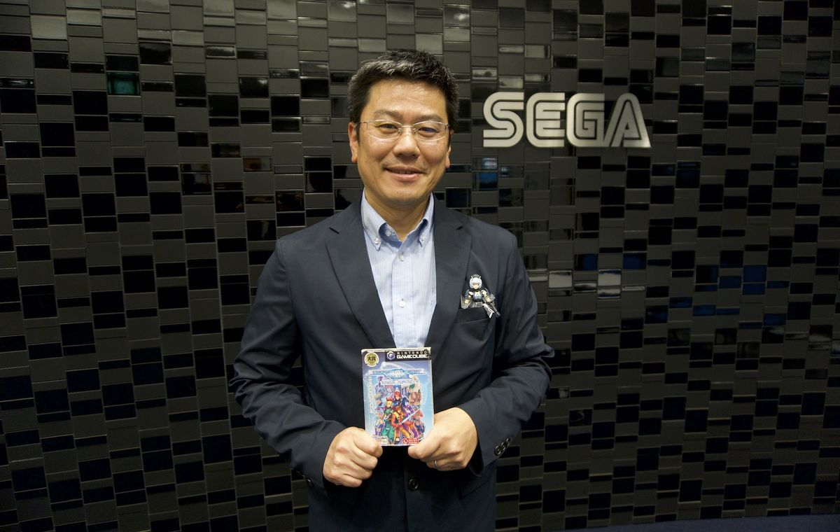Takao Miyoshi holds a GameCube copy of Phantasy Star Online in front of a wall with the Sega logo on it