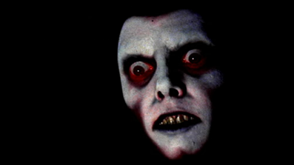 A frightening face looms out of the darkness in The Exorcist.